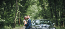 Newlyweds Near The Black Wedding Car Stand On The Road In The Summer Forest. Panorama, Copy Space.