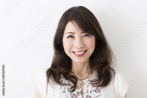 Obraz 白壁にもたれるミドル女性 - fototapety do salonu
