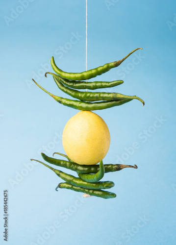lemon chilies hanging - Indian superstitious lemon and green chillies tied with thread and tied on doors at home or shop to avoid any bad fortune also known as totka or nazar battu