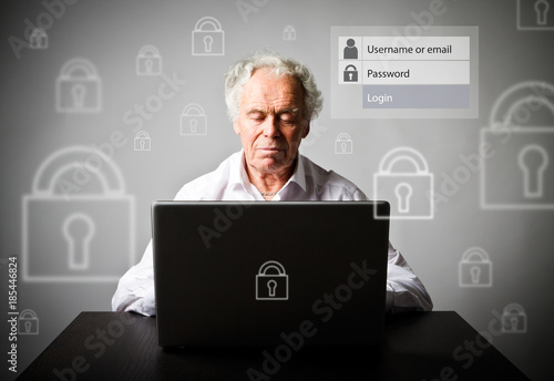 Old man using a laptop. Forgot password concept.
