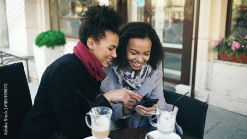 Fotografía Two attractive mixed race female friends sharing together using smartphone in st