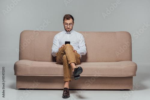 Obraz stylish man in eyeglasses sitting on couch and using smarttphone isolated on grey - fototapety do salonu