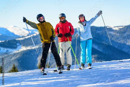 Fotografie, Obraz  Three happy skiers having fun on winter ski slope