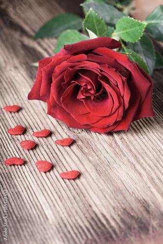 Spoed Fotobehang Rood, zwart, wit Single red rose witn small hearts on wooden background