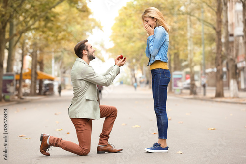 Photo Young man with engagement ring making proposal to his beloved girlfriend outdoor