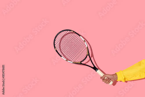 Obraz na plátně Close-up view of male hand holding tennis racket on pink background
