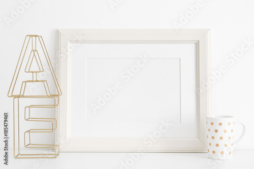 Fotografiet  Empty frame, cup and decorative letters on table near white wall