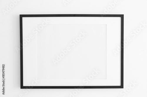 Empty black frame on white wall