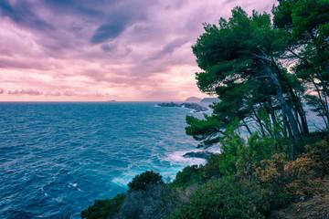 Fototapeta Morze Beautiful sunset seascape during a storm, wild sea coast with rocks and pine trees, Dubrovnik, Croatia