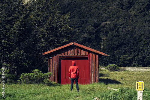 Photo Hombre delgado de espaldas vestido de rojo frente a una casa roja en medio de la naturaleza