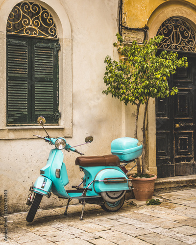 Fotoposter Scooter Corfu, Greece- December 21, 2017: Narrow streets and alleys in Corfu town Greece.Architecture in the old town of Corfu is heavily influenced my the Venetian architecture.Blue Vespa outside a building.