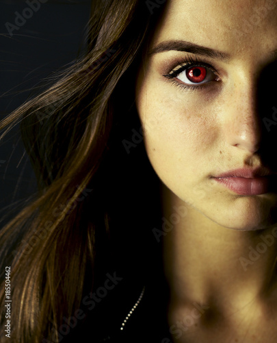 Portrait of beautiful vampire young woman with red eyes. Fotobehang