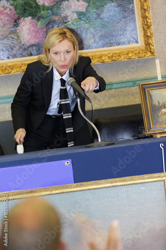 woman auctioneer selling to a bidder Wallpaper Mural