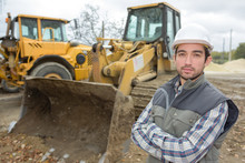 Portrait Of Construction Worker Next To Digger