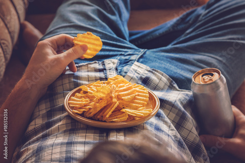 Fotografie, Obraz  After work a guy wearing shirt and jeans lying on sofa, drinking a cold beer, eating crisps and watching sport tv channel