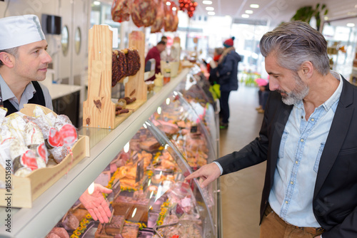 Vászonkép Man choosing from delicatessen counter
