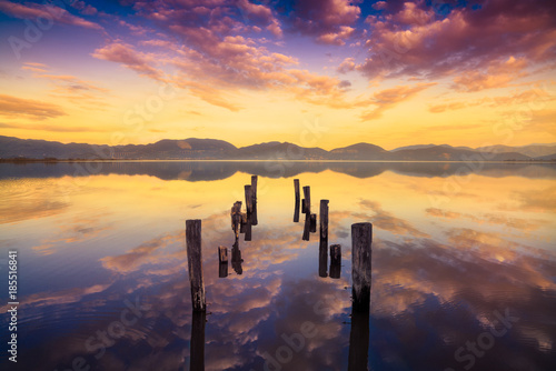 Wooden pier or jetty remains on a warm lake sunset and sky reflection on water. Versilia Tuscany, Italy