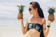 Beautiful happy female with very long hair holding pineapples on sea shore