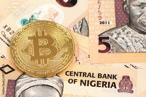 A close up image of a physical bitcoin with Nigerian Naira notes