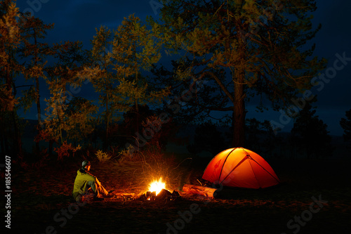 Photo Stands Camping A man sits by the fire near a tent on the shore of Lake Baikal