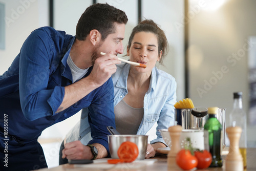 Poster Cuisine Couple at home having fun cooking together
