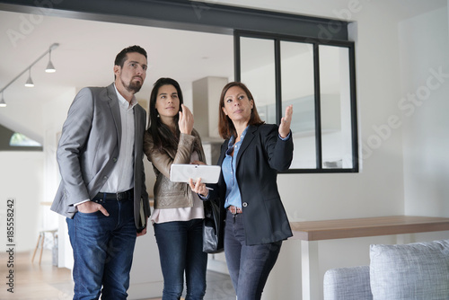 Couple with real-estate agent visiting modern house Fototapete