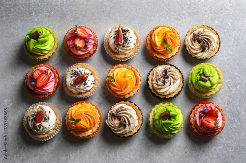 Foto auf AluDibond Desserts Tasty colorful cakes on grey background, top view