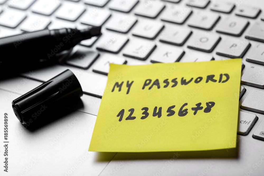 Fototapeta sticky note with weak easy password on laptop keyboard