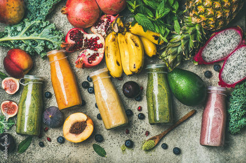Fotografía Flat-lay of colorful smoothies in bottles with fresh tropical fruit and superfoods on concrete background, top view