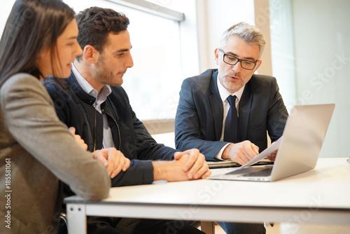 Fototapeta Young couple meeting financial advisor for home investment obraz na płótnie