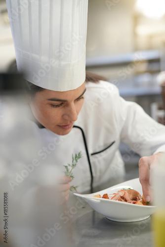Carta da parati Closeup of cook chef in professional kitchen preparing dish
