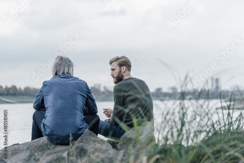 Father and son meeting at Rhine river in autmn, talking together