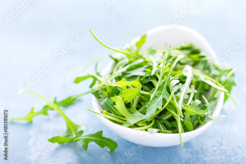 Photo Fresh arugula leaves in bowl on table. Light background, closeup