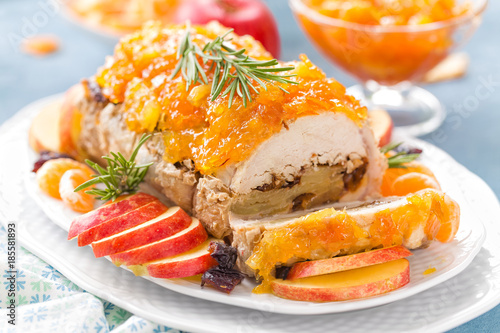 Photo  Baked meatloaf stuffed with apples and plums, decorated tangerine confiture