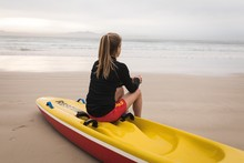 Female Lifeguard Sitting On Rescue Boat At Beach