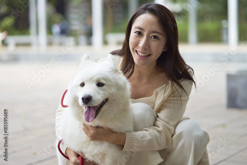 Photo  Asian beauty embracing her dog smiling at camera outdoor in garden