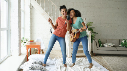 Fototapeta Mixed race young funny girls dance singing with hairdryer and playing acoustic guitar on a bed. Sisters having fun leisure in bedroom at home