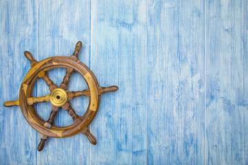 Fototapeta maritime background with helm on blue wood