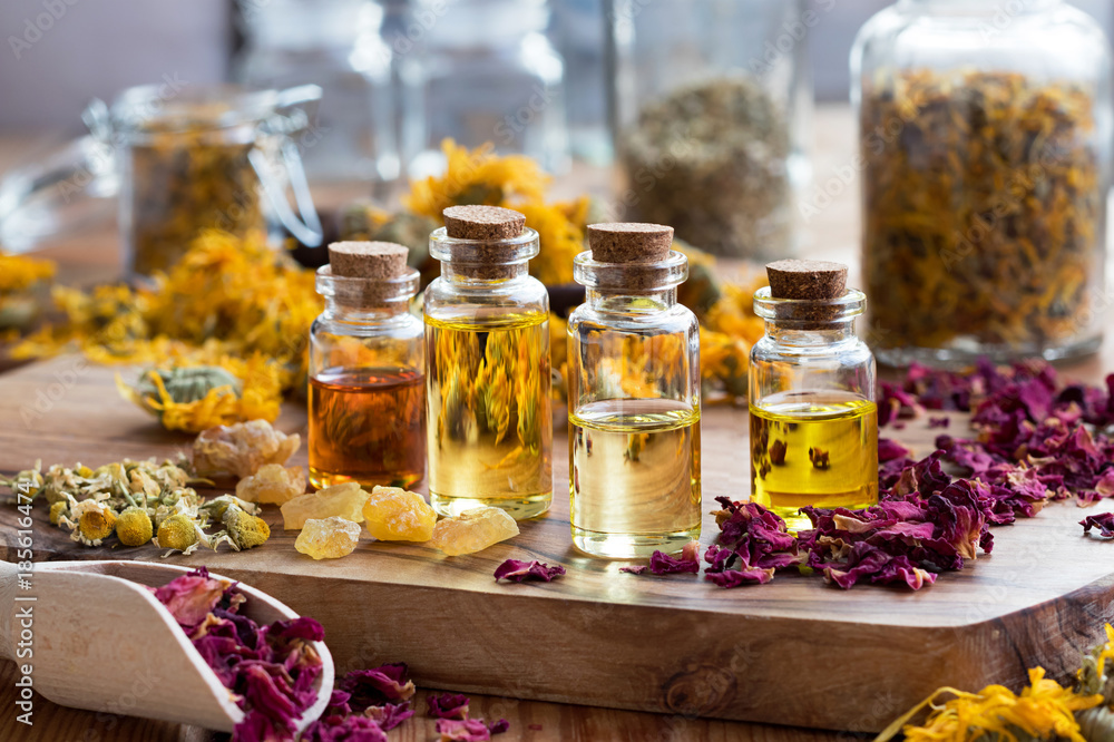 Fototapety, obrazy: Bottles of essential oil with herbs and frankincense resin