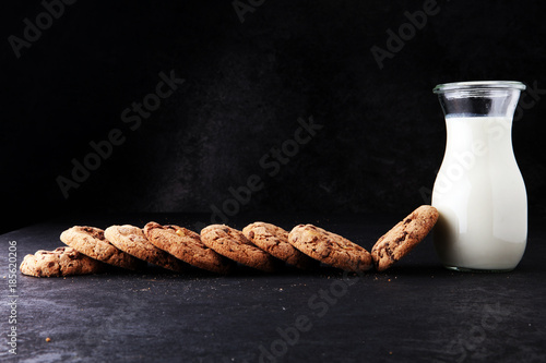Fotobehang Koekjes Chocolate chip cookies with milk on dark grey table