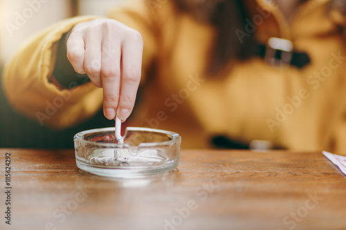 Poster de jardin Bar Focus on caucasian young woman hand putting out cigarette on glass ashtray on wooden table, cigarette butt, smoking is dying. Quit smoking. Health concept. Close up photo.