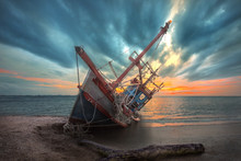 An Old Useless Fishing Boat Laying Dead On The Sea Beach At Sunset Scenery In Background