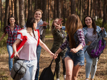 Happy Young Group Hiking Together Through The Forest. Lifestyle Of Travelers. Team Spirit.