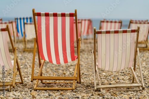 Empty deck chairs on a pebble beach faced towards the sea Wallpaper Mural
