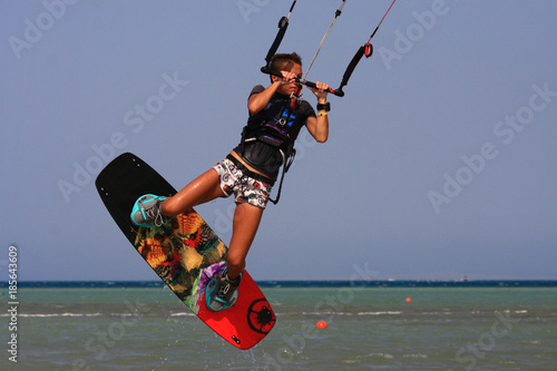 Kitesurfing girl in boots and shorts with kite in blue sky on kiteboard in the blue sea jumping air trick. Recreational activity, water sports, action, hobby and fun in summer time. Kiteboarding sport