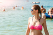 Young, beautiful girl in a bathing suit and sunglasses stands on the background of the sea. The concept of vacation, vacation, summer, vacation, travel. Copy space.