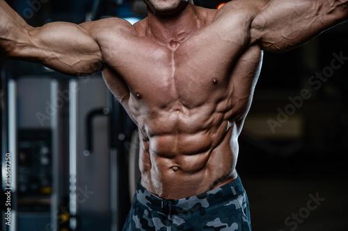 Fotomural Brutal strong bodybuilder athletic men pumping up muscles with dumbbells