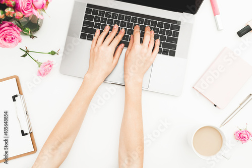 Fototapeta Flat lay home office desk. Woman workspace with female hands, laptop, pink roses bouquet, accessories, diary. Top view. Girl working on laptop. obraz na płótnie