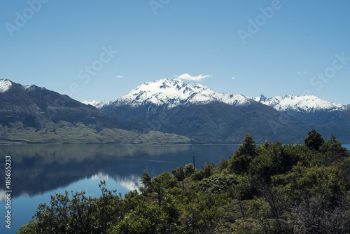 Poster Reflexion Paisaje de montañas frente a un gran lago donde se reflejan. Cielo azul despejado.
