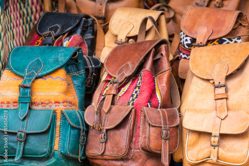 Moroccan leather goods bags and slippers at outdoor market in Marrakesh, Morocco.